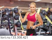 Купить «happy young woman with dumbbells exercising in gym», фото № 33308421, снято 23 марта 2013 г. (c) Syda Productions / Фотобанк Лори