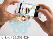Купить «hands with phone and food nutritional value chart», фото № 33308429, снято 8 декабря 2016 г. (c) Syda Productions / Фотобанк Лори