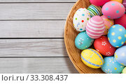 Купить «close up of colored easter eggs in wicker basket», фото № 33308437, снято 15 марта 2018 г. (c) Syda Productions / Фотобанк Лори