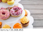 close up of glazed donuts and cupcakes on stand. Стоковое фото, фотограф Syda Productions / Фотобанк Лори