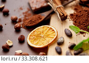 Купить «chocolate with hazelnuts, cocoa beans and orange», фото № 33308621, снято 1 февраля 2019 г. (c) Syda Productions / Фотобанк Лори
