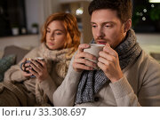 Купить «sick young couple drinking hot tea at home», фото № 33308697, снято 6 февраля 2020 г. (c) Syda Productions / Фотобанк Лори