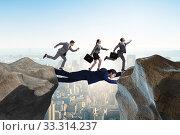 Купить «Businessman acting as a bridge in support concept», фото № 33314237, снято 3 апреля 2020 г. (c) Elnur / Фотобанк Лори