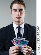 Купить «Young man in formalwear holding money.», фото № 33314561, снято 31 марта 2020 г. (c) PantherMedia / Фотобанк Лори