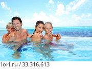 Купить «Family portrait in infinity pool», фото № 33316613, снято 8 апреля 2020 г. (c) PantherMedia / Фотобанк Лори