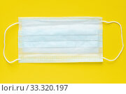 Medicine surgical face mask on yellow background. World pandemic insurance, airborne diseases, influenza, SARS. Стоковое фото, фотограф А. А. Пирагис / Фотобанк Лори