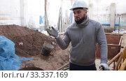 Confident young supervisor talking about process of building overhaul, comparing to blueprints. Стоковое видео, видеограф Яков Филимонов / Фотобанк Лори