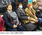 Купить «Пассажиры в метро в медицинской маске», фото № 33340561, снято 3 марта 2020 г. (c) Victoria Demidova / Фотобанк Лори