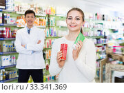 Portrait of woman client who is satisfied of recommended medicines in pharmacy. Стоковое фото, фотограф Яков Филимонов / Фотобанк Лори