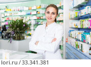 Купить «Female pharmacist standing in drugstore», фото № 33341381, снято 26 марта 2018 г. (c) Яков Филимонов / Фотобанк Лори