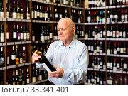 Купить «Elderly man chooses red wine in a liquor store», фото № 33341401, снято 4 апреля 2020 г. (c) Яков Филимонов / Фотобанк Лори