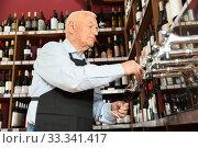 Купить «Confident elderly male winemaker pouring wine from wine column in liquor store», фото № 33341417, снято 5 апреля 2020 г. (c) Яков Филимонов / Фотобанк Лори
