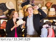 Купить «young wife and husband choosing dress hats in the store», фото № 33341629, снято 2 мая 2017 г. (c) Яков Филимонов / Фотобанк Лори