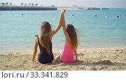 Купить «Two little happy girls have a lot of fun at tropical beach playing together», видеоролик № 33341829, снято 3 марта 2020 г. (c) Дмитрий Травников / Фотобанк Лори