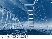 Проезд по арочному пролету нового Крымского моста, соединяющего берега Керченского пролива. Тонирование в классический синий (2018 год). Стоковое фото, фотограф Наталья Гармашева / Фотобанк Лори