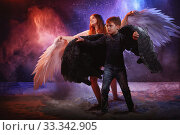 Black and white angel together on a dark background with colored lighting. The concept of war between good and evil. Girl and boy with angel wings during a photo shoot with flour and loose powder. Стоковое фото, фотограф Кривошеина Елена Леонидовна / Фотобанк Лори