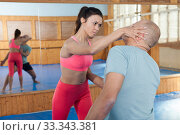 Купить «Ordinary female is fighting with trainer on the self-defense course for woman in sport club», фото № 33343381, снято 10 апреля 2019 г. (c) Яков Филимонов / Фотобанк Лори