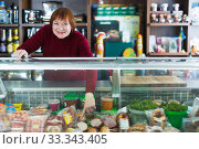 Nice seller woman offering different products. Стоковое фото, фотограф Яков Филимонов / Фотобанк Лори