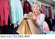 Купить «Woman consumer in the dress boutique among clothes with paper bags», фото № 33343469, снято 20 декабря 2017 г. (c) Яков Филимонов / Фотобанк Лори