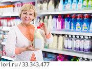 Купить «Smiling woman purchaser holding chemical goods», фото № 33343477, снято 20 декабря 2017 г. (c) Яков Филимонов / Фотобанк Лори