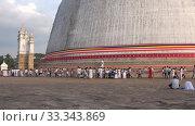Паломники у подножия древней дагобы Ruwanwelisaya. Анурадхапура, Шри-ланка (2020 год). Редакционное видео, видеограф Виктор Карасев / Фотобанк Лори