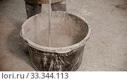 Купить «Concrete industry - worker mixing dry cement with pieces of glass», видеоролик № 33344113, снято 5 июня 2020 г. (c) Константин Шишкин / Фотобанк Лори