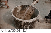 Купить «Concrete industry - worker adding water in the bucket full of dry cement», видеоролик № 33344121, снято 5 июня 2020 г. (c) Константин Шишкин / Фотобанк Лори