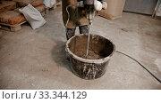 Купить «Concrete industry - mixing concrete out of cement water and pieces of glass using a hand mixer», видеоролик № 33344129, снято 5 июня 2020 г. (c) Константин Шишкин / Фотобанк Лори