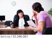 Купить «Young man consulting with judge on litigation issue», фото № 33346061, снято 6 мая 2019 г. (c) Elnur / Фотобанк Лори