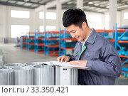 Купить «Young chinese man works in motor manufacturing factory», фото № 33350421, снято 13 июля 2020 г. (c) easy Fotostock / Фотобанк Лори