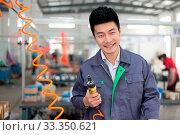 Купить «Young chinese man works in motor manufacturing factory», фото № 33350621, снято 13 июля 2020 г. (c) easy Fotostock / Фотобанк Лори