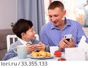 Купить «Young man and his son using phones at table with tea indoors», фото № 33355133, снято 14 июля 2020 г. (c) Яков Филимонов / Фотобанк Лори