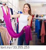 Купить «young smiling brunette selecting new dress in fashionable showroom», фото № 33355253, снято 11 апреля 2017 г. (c) Яков Филимонов / Фотобанк Лори