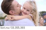 Купить «Middle-aged father embraces his daughter. Fair-haired little girl smiles happily», видеоролик № 33355393, снято 29 сентября 2019 г. (c) Ирина Мойсеева / Фотобанк Лори