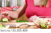 Купить «Hands of a young woman cuts a cucumber for a vegetable salad sitting at a table in the kitchen», видеоролик № 33355409, снято 8 марта 2020 г. (c) Алексей Кузнецов / Фотобанк Лори