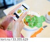 Купить «hands with food on smartphone screen at restaurant», фото № 33355629, снято 17 августа 2017 г. (c) Syda Productions / Фотобанк Лори