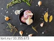 Купить «garlic in bowl and rosemary on stone surface», фото № 33355673, снято 6 сентября 2018 г. (c) Syda Productions / Фотобанк Лори