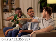 Купить «happy male friends drinking beer at home at night», фото № 33355837, снято 28 декабря 2019 г. (c) Syda Productions / Фотобанк Лори