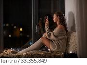 woman taking selfie with smartphone on windowsill. Стоковое фото, фотограф Syda Productions / Фотобанк Лори
