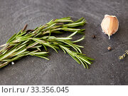 Купить «rosemary, garlic and black pepper on stone surface», фото № 33356045, снято 6 сентября 2018 г. (c) Syda Productions / Фотобанк Лори