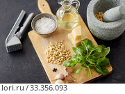 ingredients for basil pesto sauce on wooden board. Стоковое фото, фотограф Syda Productions / Фотобанк Лори