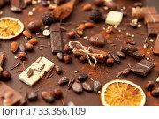 Купить «cocoa beans, chocolate, nuts and cinnamon sticks», фото № 33356109, снято 1 февраля 2019 г. (c) Syda Productions / Фотобанк Лори