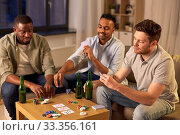 Купить «smiling male friends playing cards at home», фото № 33356161, снято 28 декабря 2019 г. (c) Syda Productions / Фотобанк Лори