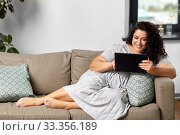 woman with tablet pc computer on sofa at home. Стоковое фото, фотограф Syda Productions / Фотобанк Лори
