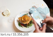 Купить «hands with phone and food nutritional value chart», фото № 33356205, снято 16 января 2017 г. (c) Syda Productions / Фотобанк Лори
