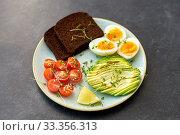 avocado, eggs, toast bread and cherry tomato. Стоковое фото, фотограф Syda Productions / Фотобанк Лори
