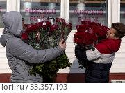 Мужчины несут купленные на Рижском цветочном рынке букеты роз в канун Международного женского дня - 8 марта в городе Москве, Россия (2020 год). Редакционное фото, фотограф Николай Винокуров / Фотобанк Лори