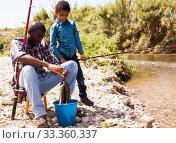 Купить «Man and boy with bucket of catch», фото № 33360337, снято 26 мая 2019 г. (c) Яков Филимонов / Фотобанк Лори