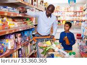 Купить «Happy friendly African family of father and tween son shopping together in supermarket», фото № 33360365, снято 15 апреля 2019 г. (c) Яков Филимонов / Фотобанк Лори