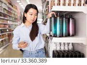 Купить «Asian girl selecting hair conditioner», фото № 33360389, снято 24 октября 2019 г. (c) Яков Филимонов / Фотобанк Лори